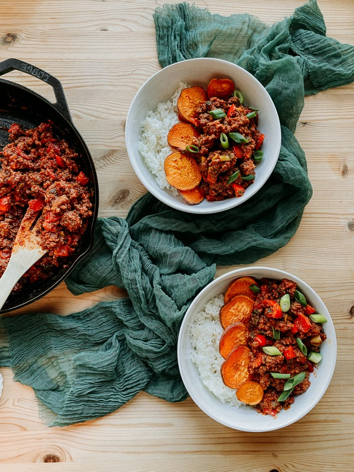 two white bowls filled with sloppy joe meat, rice, and sweet potatoes resting next to a skillet full of the meat