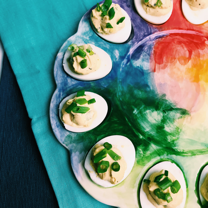 Deviled eggs topped with green onions on a rainbow dish on a blue cloth