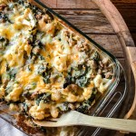 Cauliflower Mac and Cheese with Kale and Sausage in a glass baking pan with a wooden spoon