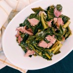 collard greens and ham hock in a white bowl ona dark blue background with white and yellow towel