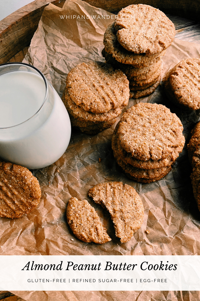 a glass of milk and piles of Almond Peanut Butter Cookies on brown parchment paper