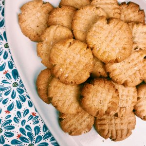 almond peanut butter cookies ona white platter on a floral background