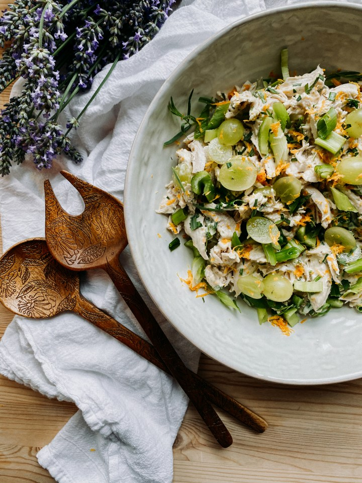 french chicken salad in a white bowl with wooden serving utensils nearby and a bit of fresh lavender in the frame