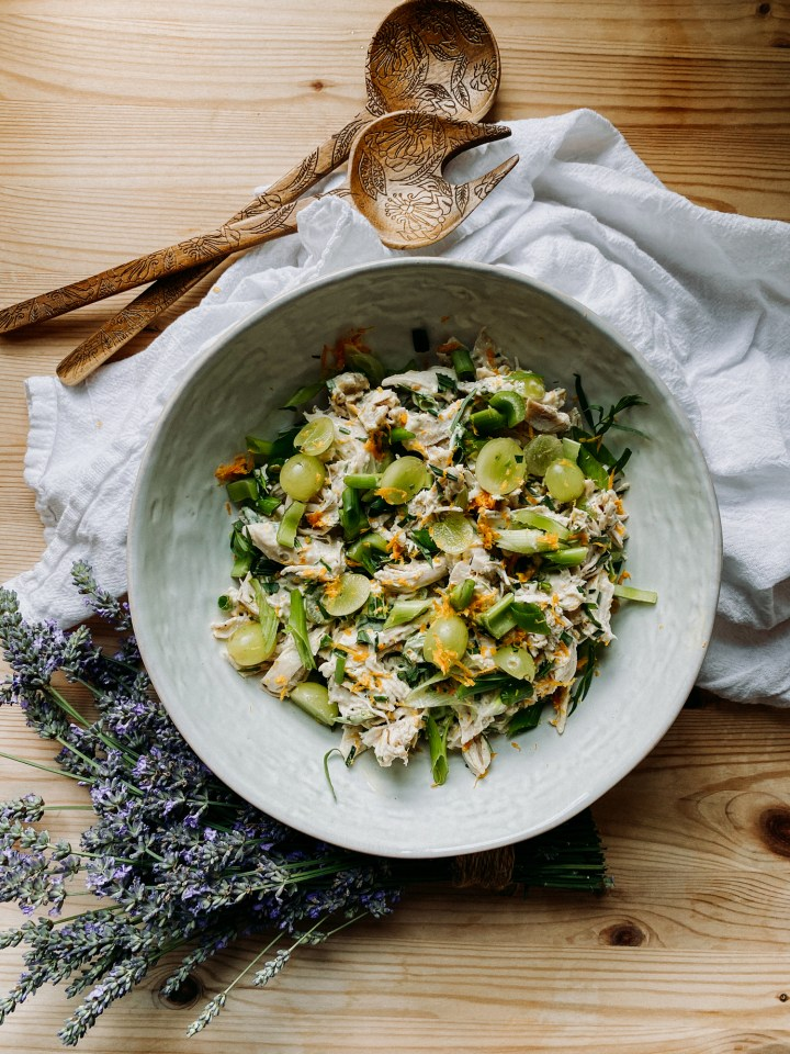 French chicken salad in a white serving bowl with a bunch of fresh lavender resting beneath the bowl and a white towel underneath with two wooden serving utensils resting on top