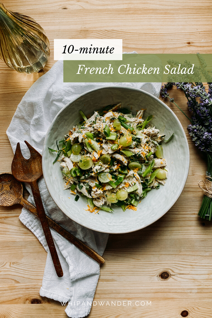 chicken salad with herbs de provence and grapes in a white serving dishw ith wooden serving spoons and a white towel nearby