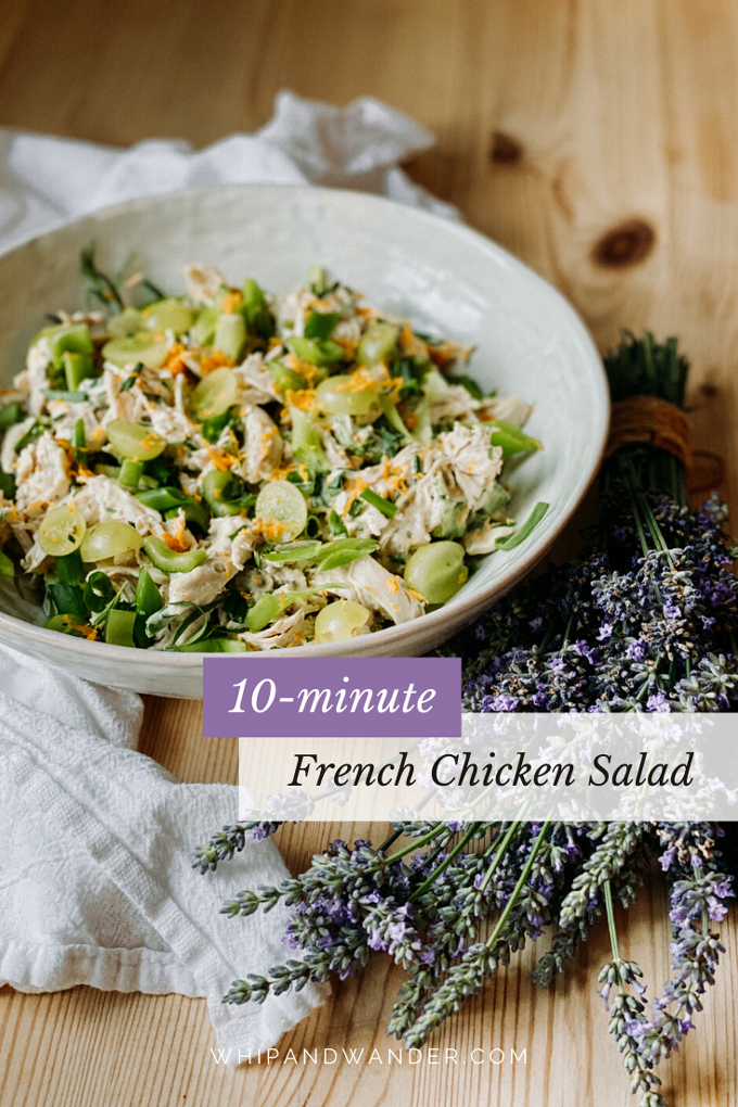 a side shot of a bowl of chicken salad with herbs, fruit, and lavender