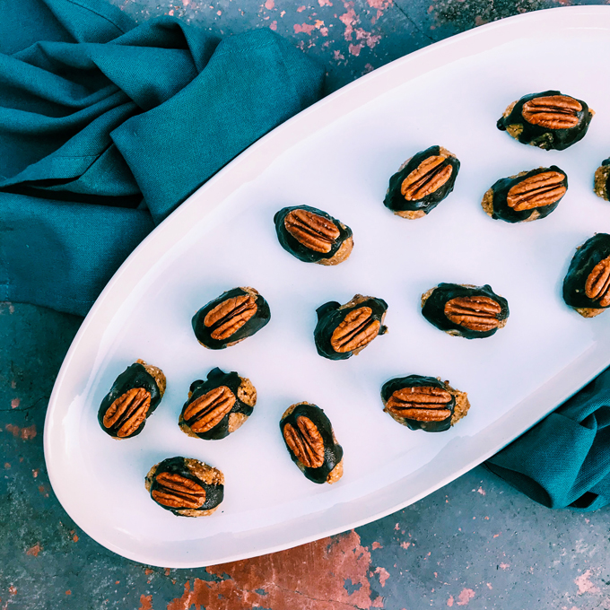 A white plate with nut clusters and chocolate and pecans on a teal towel