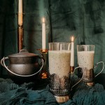 two glasses of Polyjuice Potion Smoothie next to a small black cauldron and several lit candles