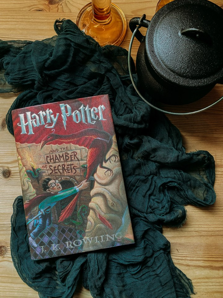Harry Potter and the chamber of secrets book resting on a dark green towel on a wooden surface next to a small black cauldron