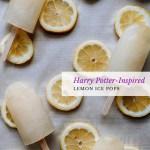 lemon popsicles resting on top of lemon slices on a parchment paper lined surface