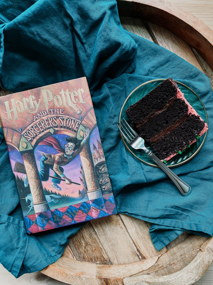 a dark green and blue towel with a harry potter book and a slice of chocolate cake on a green plate sitting on top