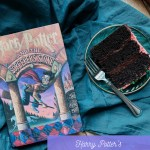 a slice of chocolate birthday cake with pink icing on a green plate with a fork, sitting next to a harry potter book resting on a dark teal towel
