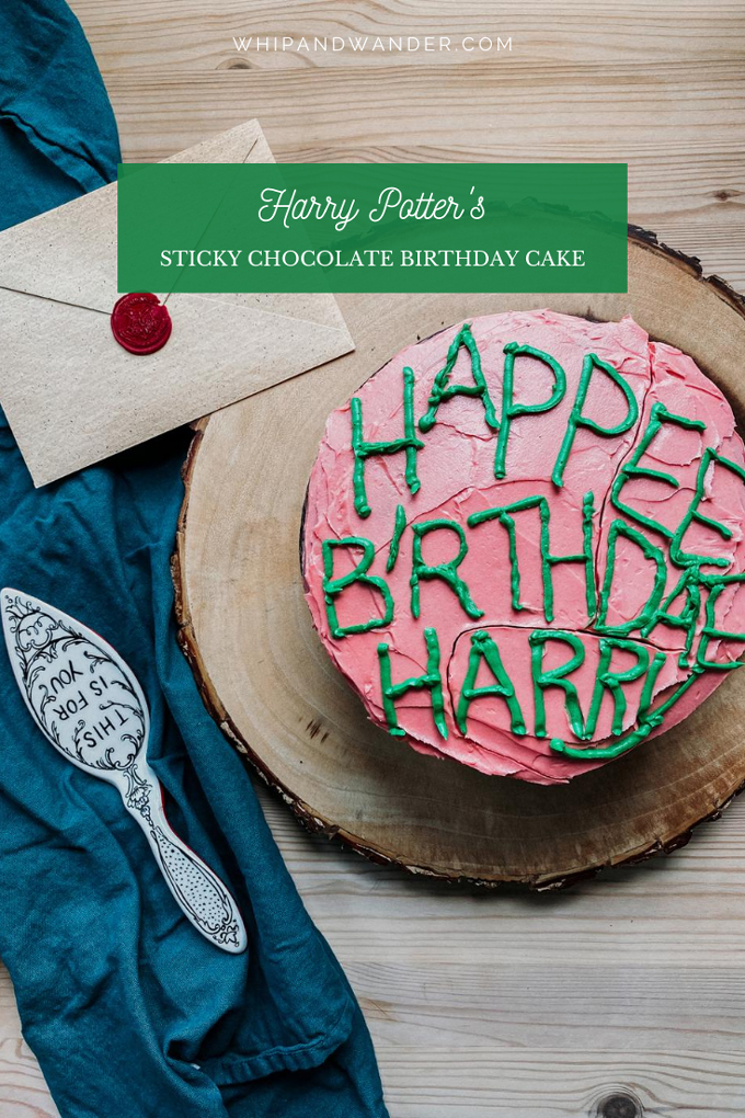 a pink frosted chocolate cake with green lettered icing on a gluten free chocolate cake with a dark blue green towel, an envelope, and a cake server resting nearby