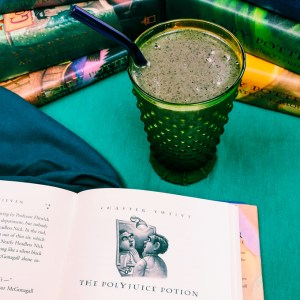 a green smoothie in front of a snack of books with a teal background
