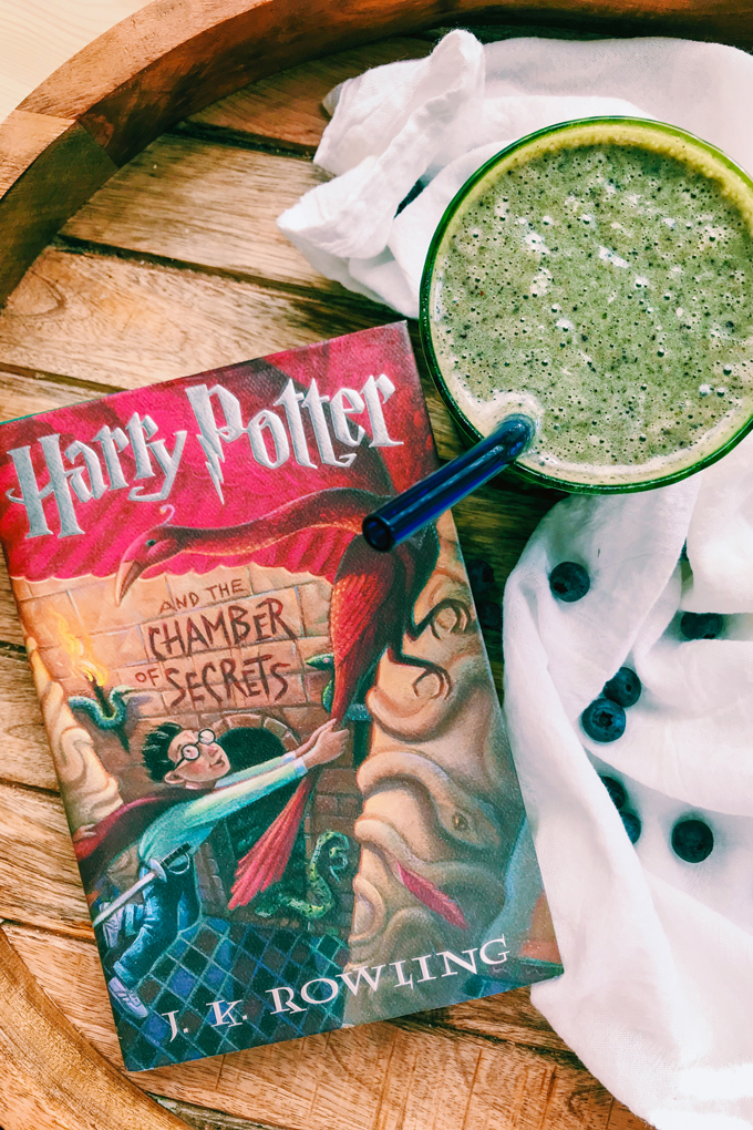 Harry Potter and the chamber of secrets book next to a green smoothie and a white towel
