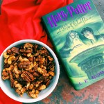 a white bowl of candied roasted nuts on a bright red towel with a green harry potter book