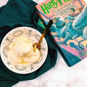 butterbeer frozen custard scoops in a bowl with a harry potter book next to it and a dark teal towel