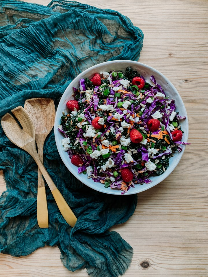 Creamy Kale Salad with Raspberries and Feta ina. white bowl resting on a dark teal cloth with wooden serving utensils resting to the left of the bowl