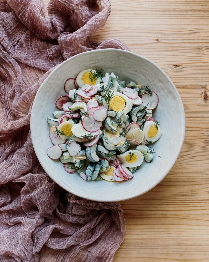 Creamy Cucumber Radish Salad in a white bowl resting on a wooden surface with a light purple cloth