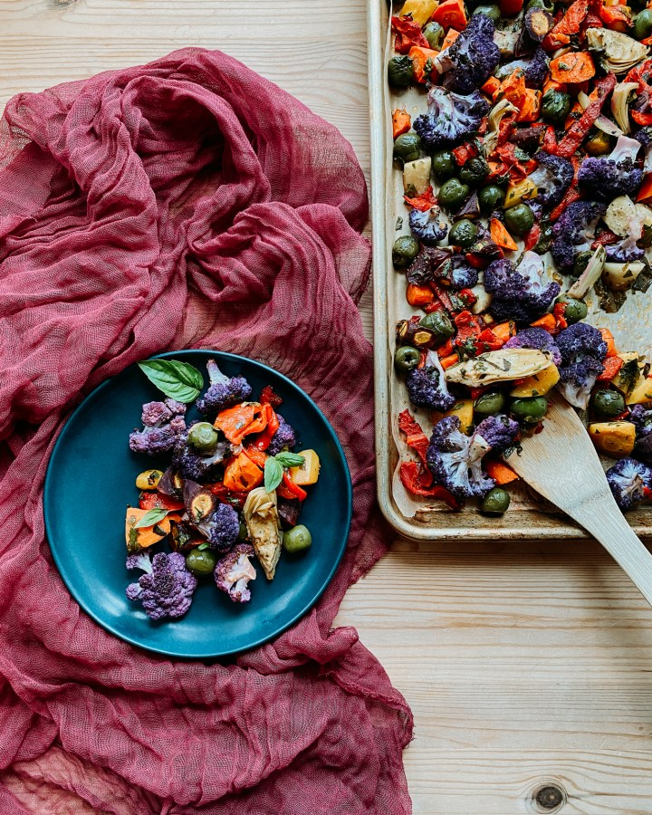 A sheet pan with Mediterranean Roasted Rainbow Vegetables and a wooden spoon next to a blue plate with the same vegetables resting on a red cloth