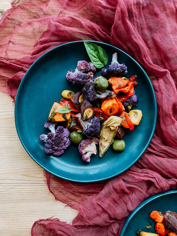 a blue plate with roasted rainbow veggies on a red cloth