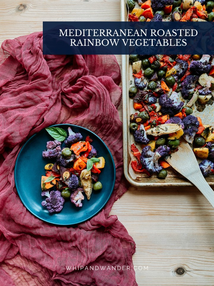a blue plate resting next to a sheet pan, both containing Mediterranean Roasted Rainbow Vegetables