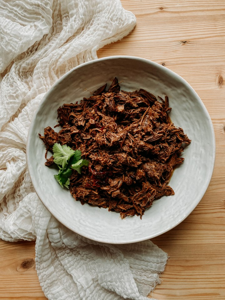Pressure Cooker Barbacoa Beef in a white bowl topped with cilantro on a wooden surface