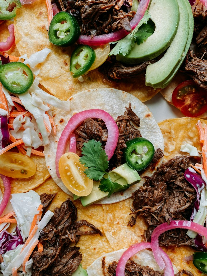 Corntortilla tacos with Pressure Cooker Barbacoa Beef, avocado, red onions, tomatoes, and jalapenos