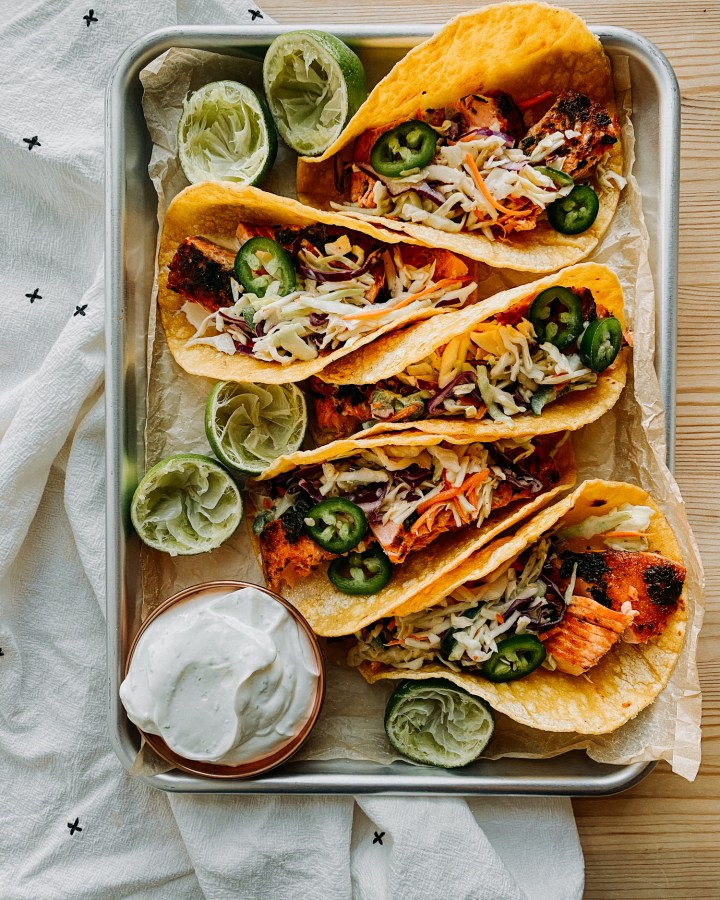 Salmon Tacos with Spicy Cabbage Slaw and Lime Crema on a sheet pan with a dish filled with lime crema