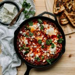 a cast iron skillet of shakshuka topped with feta and cilantro resting on a wooden surface with a wooden cutting board with sourdough toast and a white towel with a plate of feta cheese nearby