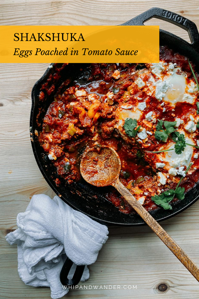 a pan of shakshuka stew with feta and cilantro, a wooden spoon testing in the pan and a white towel wrapped around the handle