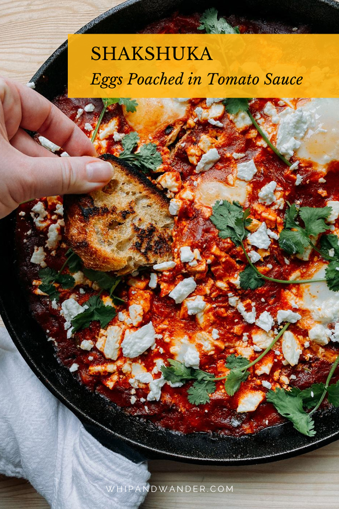 a hand holding a piece of toast which is dipping into a pan of shakshuka with cilantro and feta on top