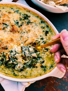 Keto Artichoke Spinach Dip being spooned up by a gold spoon, dark background