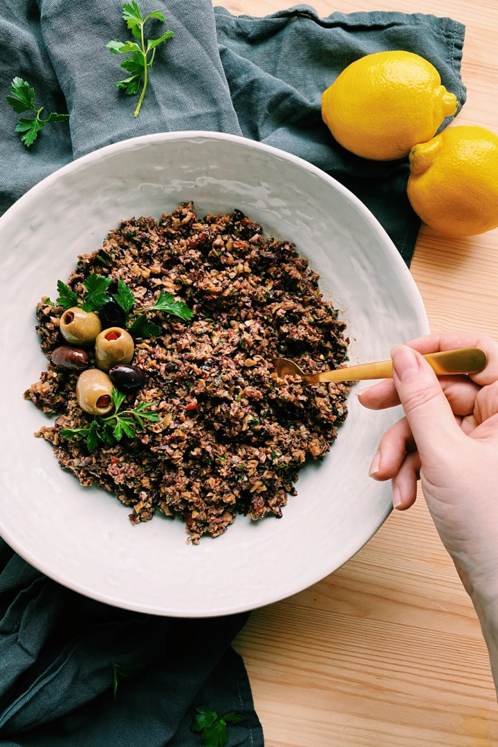 a hand spooning Olive Tapenade from a white dish
