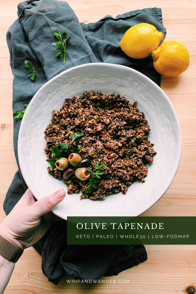 a hand holding a white bowl filled with Olive Tapenade over the top of a wood surface and a blue towel