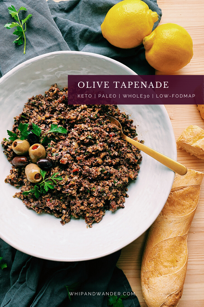 a white bowl containing Olive Tapenade, olives, and italian aprsley with a gold spoon resting int he dish with a baguette near the bowl and olives resting on the side