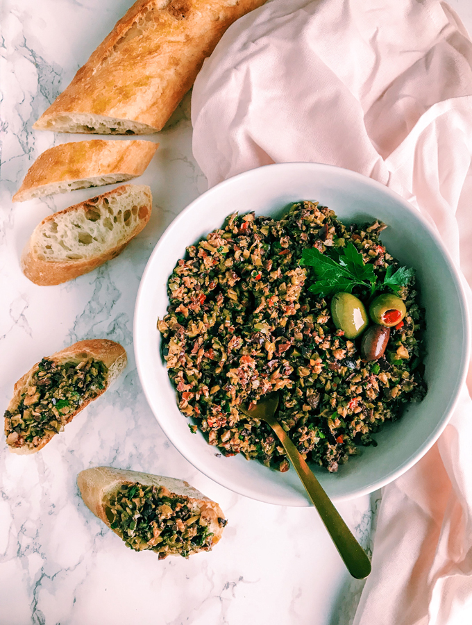 Olive Tapenade in a white bowl with bread and a pink towel