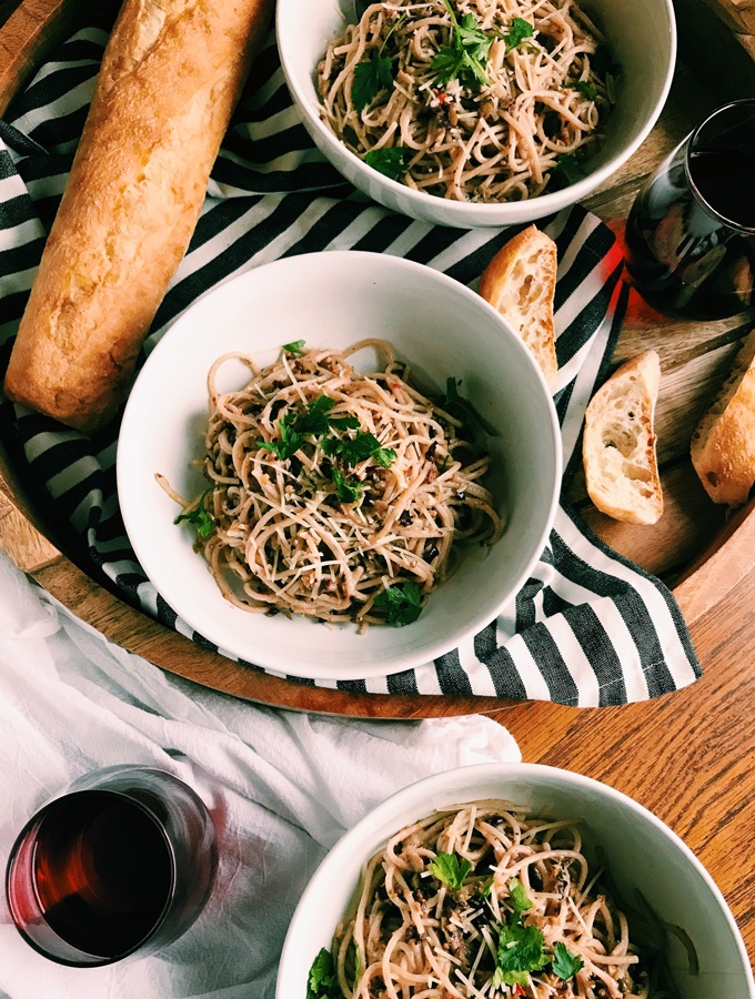 three bowls pasta with olive tapenade in white bowls with wine and bread