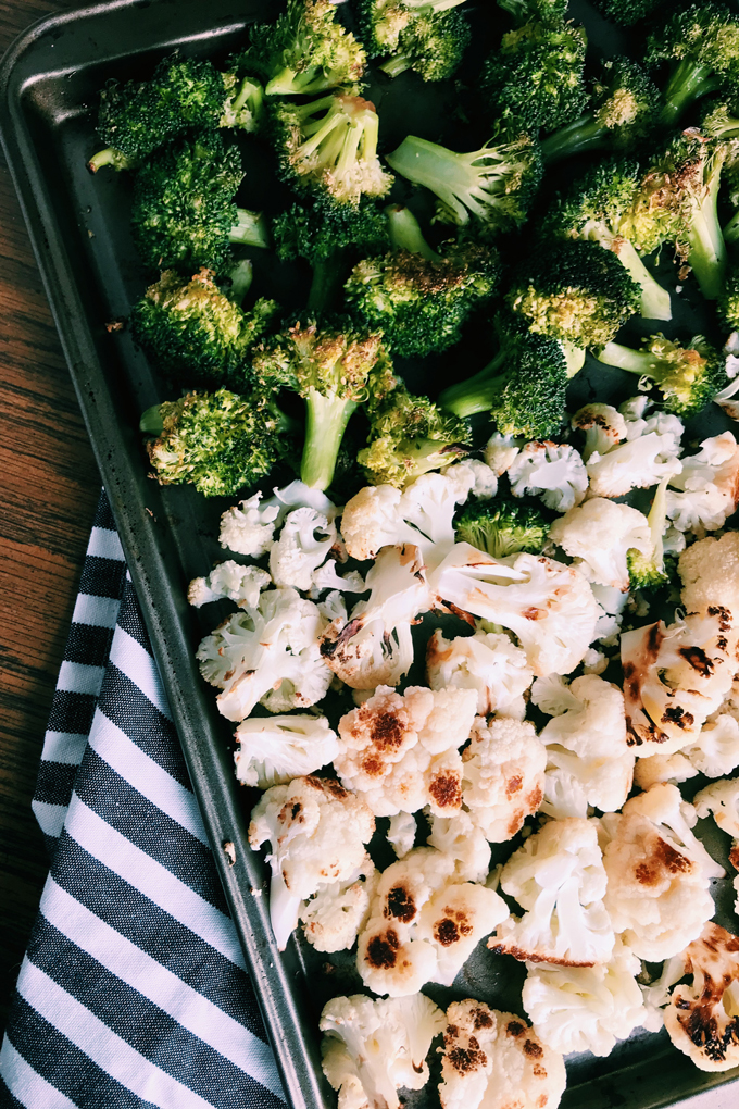roasted broccoli and cauliflower on a baking sheet with a black and white striped towel underneath