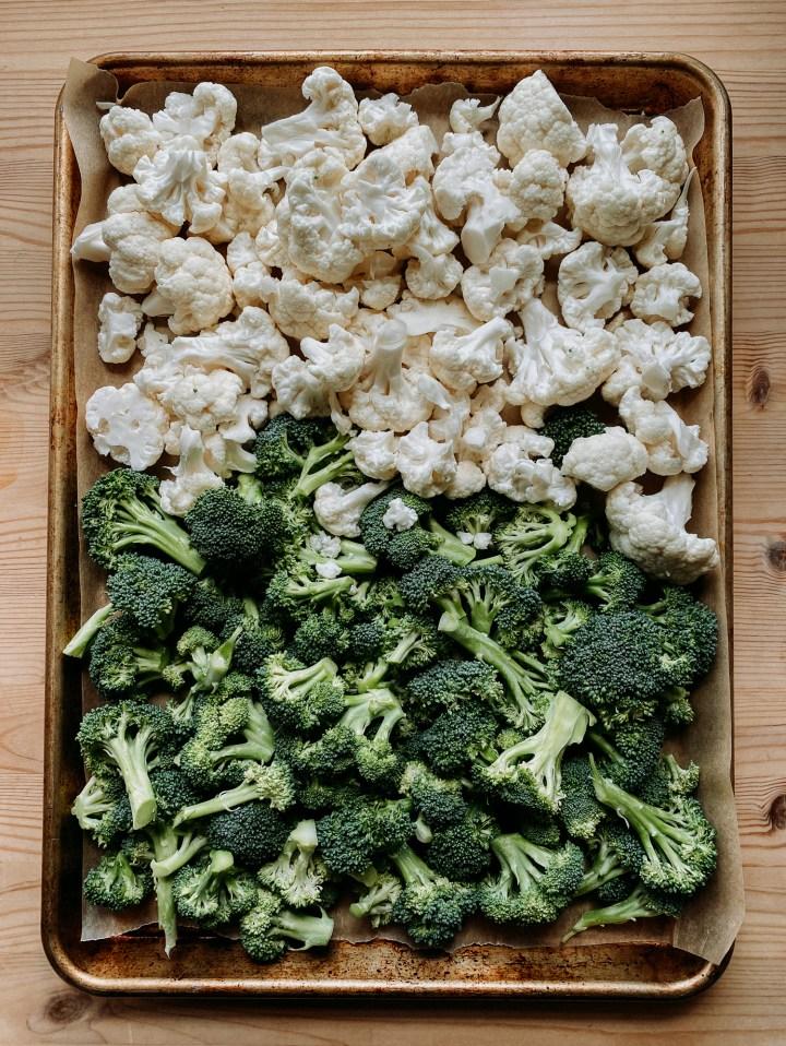 a sheet pan containing raw broccoli and cauliflower