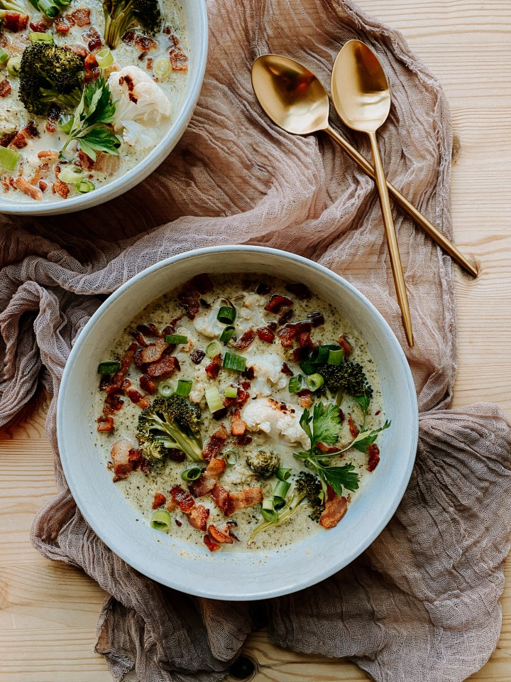 a white bowl filled with Roasted Broccoli Cauliflower Soup topped with bacon, parsley, and green onions