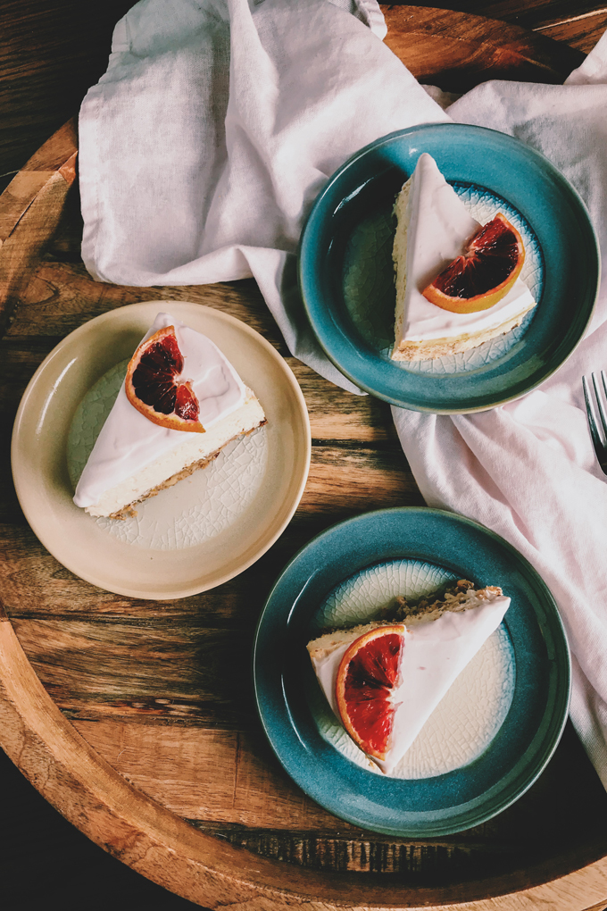slices of blood orange cheesecake on beige and teal plates