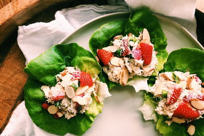 closeup of chicken salad with strawberries on butter lettuce on a white plate