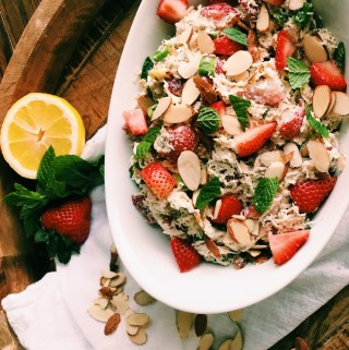 white dish with chicken salad, strawberries, poppy seeds, with mint and lemon on the side