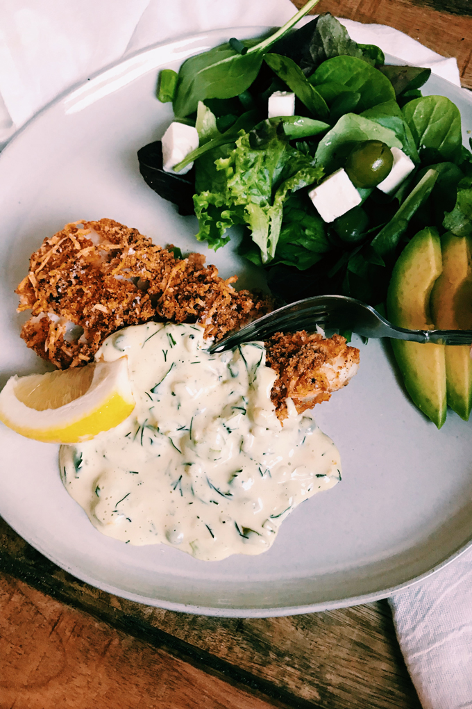 a fork cutting into Crispy Oven Fried Fish and tartar sauce with salad