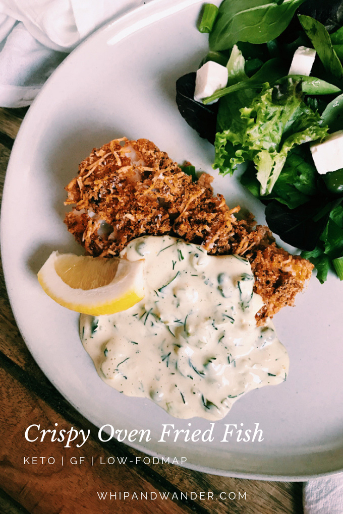 Crispy Oven Fried Fish with salad, tartar sauce, and lemon on a white plate