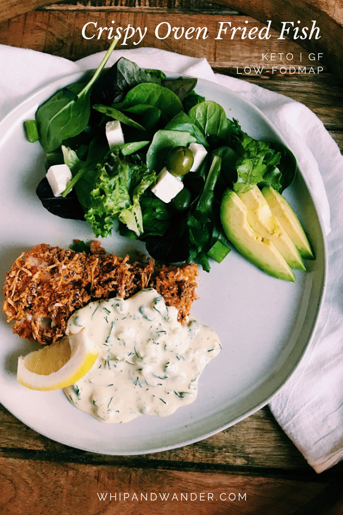 salad with avocado and fried fish with sauce and lemon on a plate