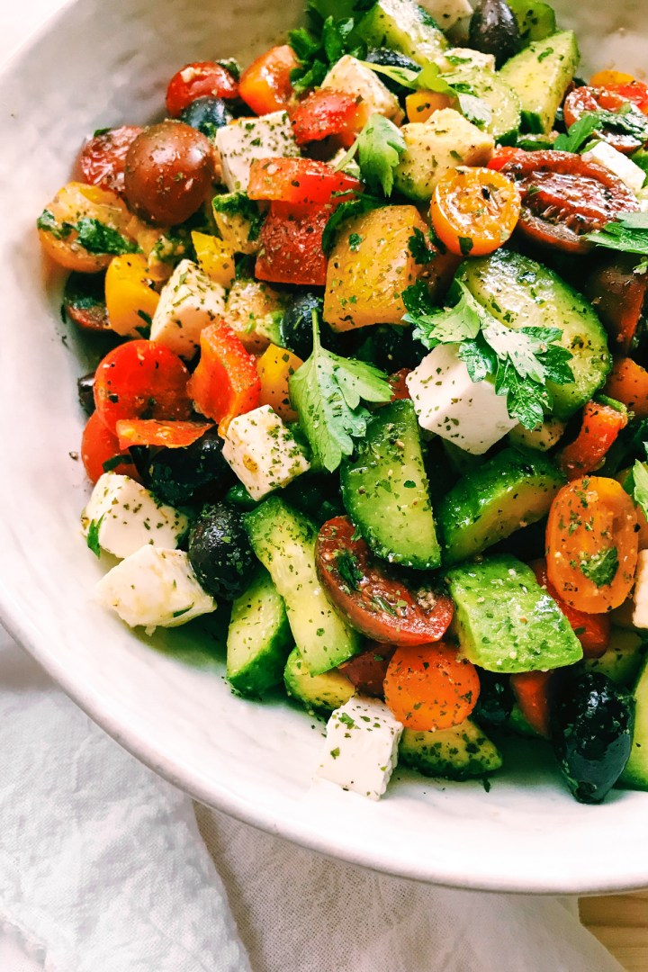 cubes of fets among a chopped veggie salad with cucumbers, tomato, olives, and peppers ina white dish