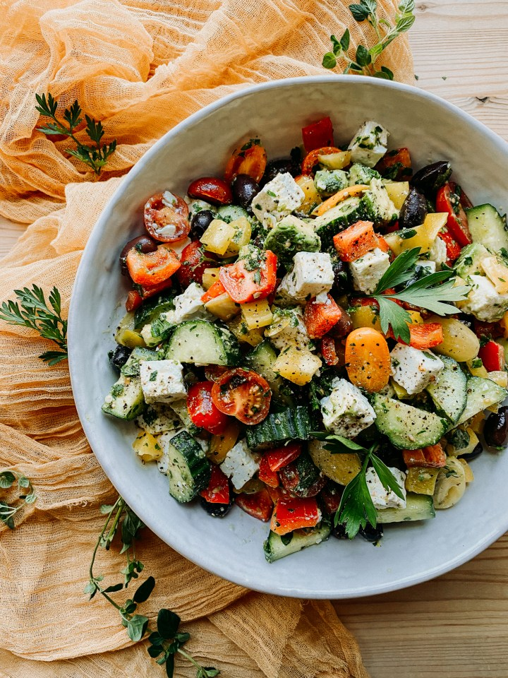 Crunchy Greek Salad in a white serving bowl with feta and avocado