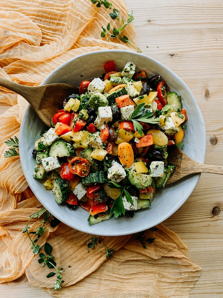 a large white serving bowl with Crunchy Greek Salad and two wooden salad servers in the bowl scooping up salad